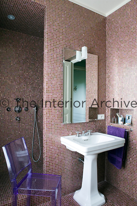 A vivid note of contrast is created by a purple plastic chair against the subtle green and pink mosaic tiles of the bathroom