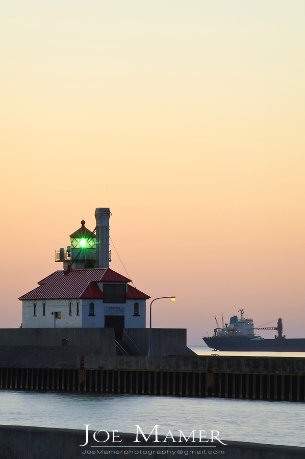 A ship awaits entry into Duluth Harbor outside of the canal breakwater at dawn in Duluth, Minnesota.