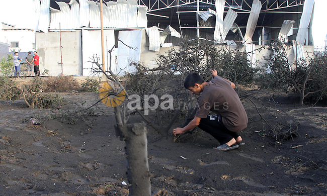A Palestinian man inspects the site of an Israeli air-strike in Gaza City on June 20, 2014. The Israeli army's air force has conducted several air raids on the besieged Gaza Strip, leaving at least seven Palestinians, including four children injured, medical sources said. Photo by Mohammed Asad
