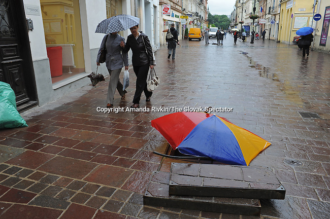 Workers cover a gap in the sidewalk with an umbrella to prevent flooding while at work nearby on a street in the historic center of Kosice, Slovakia on June 1, 2010.