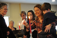 NWA Media/ANDY SHUPE - Spiritual leader Annette Olsen, left, watches as Suzie Sanford of Fayetteville, center, lights a piece of paper while holding her son, Grady Sanford, 4, Sunday, Dec. 28, 2014, as they take part in a burning bowl and communion ceremony at Unity of Fayetteville. The ceremony was a chance for members to write down and burn a word signifying that which they wish to leave behind as the new year approaches.