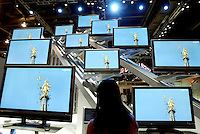 January 7,2006 , Las Vegas,Nevada --- An attendee looks at the display of Sharp Aquos flat screen televisions at the 2006 International Consumer Electronics Show (CES) at the Las Vegas Convention Center. The latest technology from 2,500 global companies is exhibited with over 130,000 attendees expected for the duration of the show held January 5-8, 2006.  ---  Chris Farina