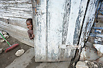 A child peeks from behind the door into their house in Batey Bombita, a community in the southwest of the Dominican Republic whose population is composed of Haitian immigrants and their descendents.
