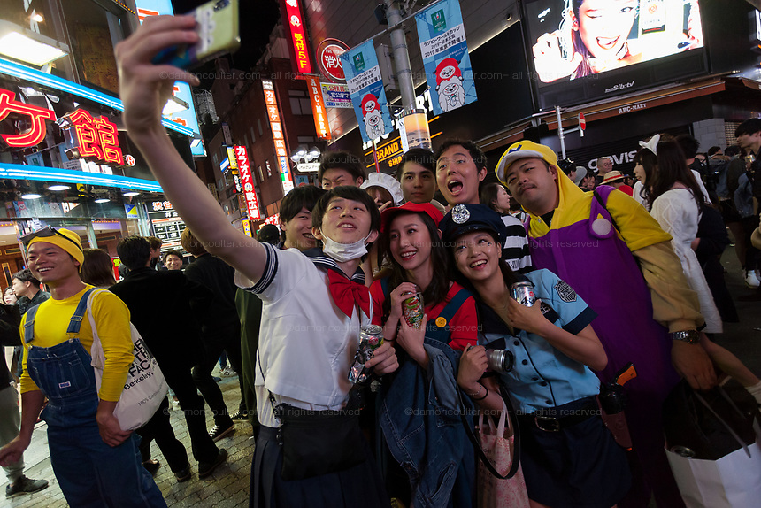 Young Japanese men and women take a selfie during the Halloween celebrations Shibuya, Tokyo, Japan. Saturday October 27th 2018. The celebrations marking this event have grown in popularity in Japan recently. Enjoyed mostly by young adults who like to dress up, drink , dance and misbehave in parts of Tokyo like Shibuya and Roppongi. There has been a push back from Japanese society and the police to try to limit the bad behaviour.