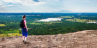 Panoramic photo of a tourist admiring the landscape of Sri Lanka from Pidurangala Rock, North Central Province, Sri Lanka. This is a panoramic photo of a female tourist admiring the landscape of Sri Lanka from Pidurangala Rock, North Central Province, Sri Lanka.