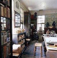 A collection of model houses made by Randolph Martz on a shelving unit in his draughting room