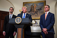 United States President President J. Donald Trump makes an announcement on the introduction of the Reforming American Immigration for a Strong Economy (RAISE) Act with US Senator Tom Cotton (Republican of Arkansas), left, and US Senator David Perdue (Republican of Georgia), right, in the Roosevelt Room at the White House in Washington, D.C., U.S., on Wednesday, August 2, 2017. The act aims to overhaul U.S. immigration by moving towards a &quot;merit-based&quot; system. <br /> Credit: Zach Gibson / Pool via CNP /MediaPunch