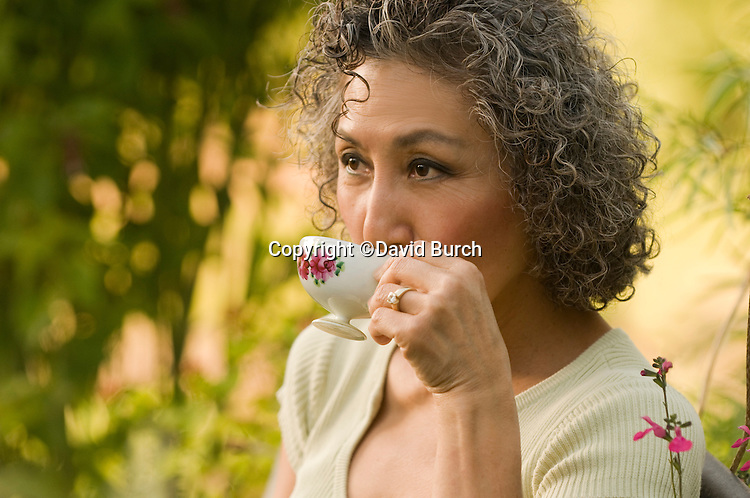Asian woman drinking tea and contemplating