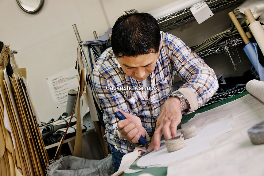 MAY 15, 2014 - KOJIMA, KURASHIKI, JAPAN: Kengo Oshima cuts Denim fabric for hand made ordered jeans at the Betty Smith's factory. (Photograph / Ko Sasaki)