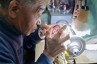 An artisan works on sake flashes decorated using Edokiriko technique. Shimizu Glass, Tokyo, Japan, January 14, 2015. Edokiriko is a style of cut glass that dates back to 1834 and is similar to British cut glass. It makes use coloured glass and highly-intricate Japanese motifs.