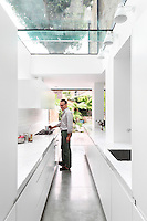 Giovanni Brighi in his modern galley kitchen in an extension with a glass roof.