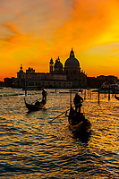 Gondolas cross the Venice Lagoon with Basilica di Santa Maria della Salute in background, Venice, Italy.