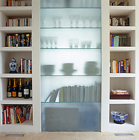 In the living room one side of a system of two-way shelving provides space for books, ornaments and wine bottles whilst the shadowy outlines from the reverse form a decorative element