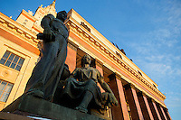 Socialist realist sculptures depicting students stand in front of the main building of Moscow State University in Moscow, Russia.