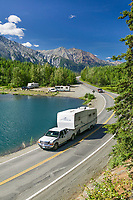 Vehicles travel by Long lake, adjacent to the Glenn Highway, Chugach mountains. Alaska