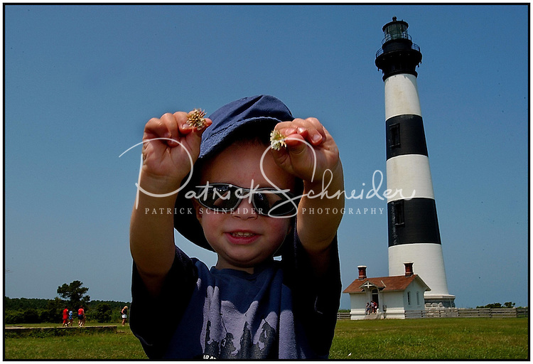 A young boy / toddler shows off two clover flowers he found near the Bodie Island Light House in the North Carolina Outer Banks. Photo is model released.