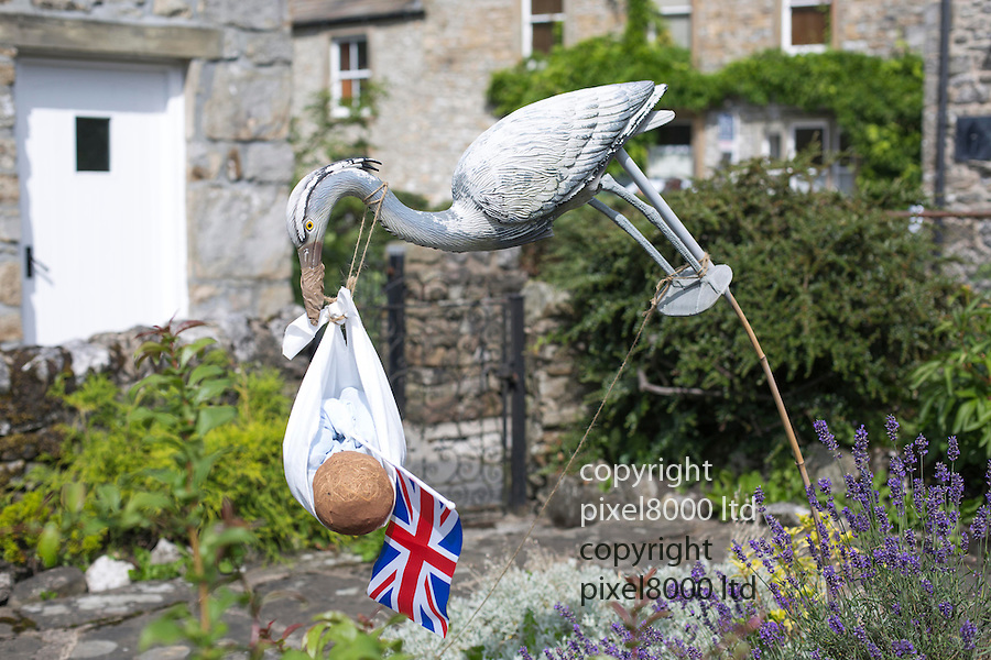 Scarecrow Festival at Kettlewell in Yorkshire 2013<br /> <br /> Royal baby scarecrow with a stork<br /> <br /> Scarecrows are made by local community and places in and around their front gardens.  Competition is fierce but it's all to raise money  for the local church  and other local projects to benefit the whole community.<br /> <br /> <br /> <br /> Picture by Gavin Rodgers/ Pixel 8000 <br /> <br /> 07917221968