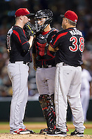 Rochester Red Wings pitching coach Marty Mason (38) has a meeting on the mound with relief pitcher Matt Hoffman (21) and catcher Eric Fryer (25) during the game against the Charlotte Knights at BB&T Ballpark on June 5, 2014 in Charlotte, North Carolina.  The Knights defeated the Red Wings 7-6.  (Brian Westerholt/Four Seam Images)