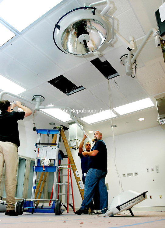 WATERBURY, CT -17 JUNE 2005-062405SV03- from left; Martin Balleux, Matt Morris and Joe Veneziano install lights in the new operating room for open heart surgery at St. Mary's Hospital in Waterbury Friday.<br /> Steven Valenti Photo <br /> (Martin Balleux, Matt Morris and Joe Veneziano,(cq))