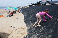 Charlott Crete, 9, of Saint-Sauveur, Quebec, Canada, climbs up a recently-repaired portion of the parking lot embankment at Herring Cove Beach in the Cape Cod National Seashore outside of Provincetown, Mass., USA, on Fri., July 1, 2016. Portions of the parking lot have been closed after land eroded during storms earlier this year.
