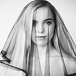 Teenager with blonde hair looking at camera wearing a veil