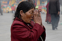 Women praying in front of a giant Incense burner in the streets of Lhasa Tibet