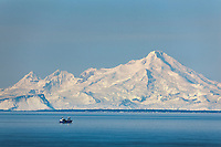 Marine vessel travels through Cook Inlet. Mount Iliamna volcano, Aleutian mountain range, Alaska Peninsula, Southcentral, Alaska.