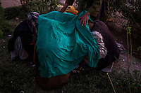 HERAT, AFGHANISTAN - OCTOBER 05, 2013: A man helps his friends cover up to maximise the effect of thr drug, trapping the smoke under a cloth as they smoke opium in a public garden in Herat City. <br /> <br /> CREDIT: Daniel Berehulak for the New York Times