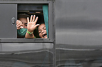 CALI - COLOMBIA, 14-04-2020: Una mujer y un hombre mueven sus manos para despedirse y dar gracias a los colombianos desde un bus durante la jornada de repatriación de 215 venezolanos hacía su país desde Cali en el día 22 de la cuarentena total en el territorio colombiano causada por la pandemia  del Coronavirus, COVID-19. / A woman and a man waves their hands to say goodbye and give thanks to the Colombians from the bus during the repatriation journey of 215 Venezuelans to their country from Cali during the day 22 of total quarantine in Colombian territory caused by the Coronavirus pandemic, COVID-19. Photo: VizzorImage / Gabriel Aponte / Staff