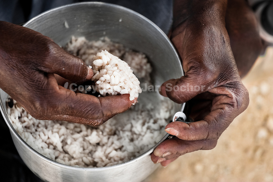 An Haitian woman eats rice in the slum of Cité Soleil, Port-au-Prince, Haiti, 17 July 2008. Rice is a basic source of nutrition for all Haitians. Cité Soleil is considered one of the worst slums in the Americas, most of its 300.000 residents live in extreme poverty. Children and single mothers predominate in the population. Social and living conditions in the slum are a human tragedy. There is no running water, no sewers and no electricity. Public services virtually do not exist – there are no stores, no hospitals or schools, no urban infrastructure. In spite of this fact, a rent must be payed even in all shacks made from rusty metal sheets. Infectious diseases are widely spread as garbage disposal does not exist in Cité Soleil. Violence is common, armed gangs operate throughout the slum.