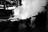 Norilsk, Russia  .May-June 1997.Melted nickel is poured from a blast furnace into hot ingot molds. Norilskyi Nickel workers cool and remove the hot ingots from the molds. Norilsk is built on the Siberian permafrost and has a vast nickel reserve..