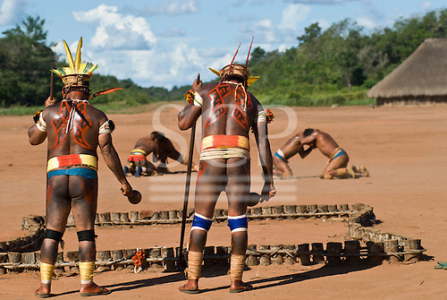 Xingu Indigenous Park, Mato Grosso State, Brazil. Aldeia Waura; two cantors chanting over the grave of a recently deceased elder, using gourd rattles, while warriors practice Huka-Huka wrestling during the funeral celebrations for the spirit of the dead man.