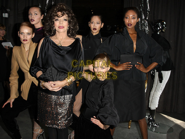 JOAN COLLINS & models .Lloyd Klein Couture Fall 2010 Presentaion A Parisian Afternoon Hosted Joan Collins held At The Lloyd Klein House of Couture, Los Angeles, California, USA, 24th March 2010..half length black top slit shoulders gold skirt  bracelets clutch bag crochet lace .CAP/ADM/KB.©Kevan Brooks/AdMedia/Capital Pictures.