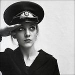 A young woman dressed in a military hat