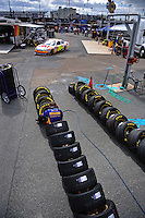Sept. 20, 2008; Dover, DE, USA; A crew member for Nascar Sprint Cup Series driver Jamie McMurray (not pictured) checks tire pressures on Goodyear tires as Greg Biffle drives past during practice for the Camping World RV 400 at Dover International Speedway. Mandatory Credit: Mark J. Rebilas-