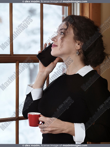 Woman with a cup of coffee talking on the phone by a window with a snowy winter scenery behind it. Apple iPhone 7 plus.