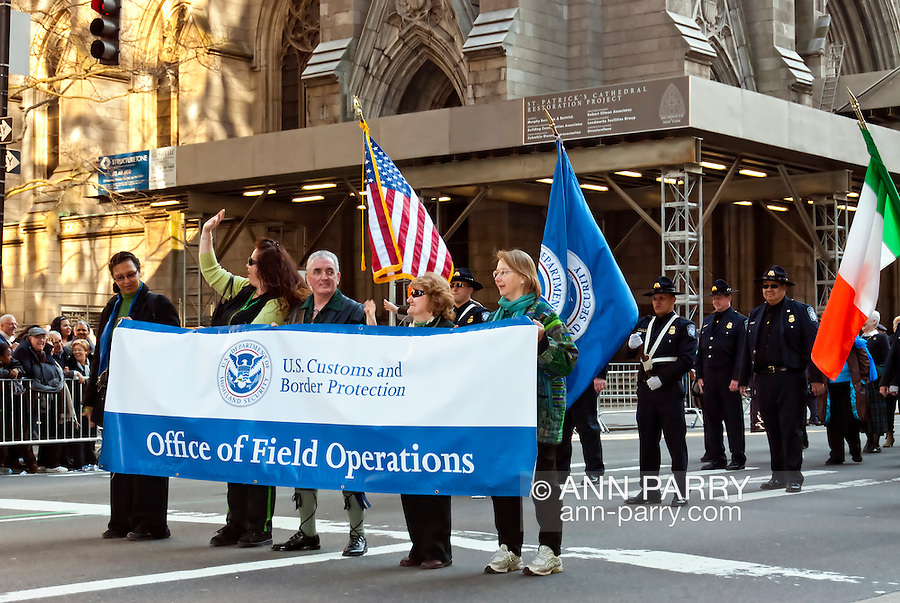 MARCH 17, 2011 - MANHATTAN: Marchers from U.S. Customs and Border Protection Office of Field Operations in St. Patrick's Day Parade in front of St. Patrick's Cathedral on 5th Avenue Manhattan, with big banner and flags.