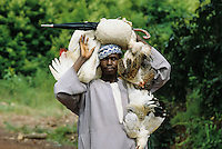 This man is going to the market to sell the  chicken bought in the near village
