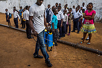 MONROVIA, LIBERIA - FEBRUARY 18: Humphrey, a caretaker, sprays the grounds with a concentrated chlorine solution, prior to the start of morning assembly on the third day of classes, since schools closed 6 months ago, due to the Ebola outbreak, at the C.D.B. King Elementary School on February 18, 2015 in Monrovia, Liberia. Though Ebola cases have receded into the single digits in Liberia, lingering fear and a depressed economy have dampened the turnout at schools. Many have yet to reopen, having failed to meet the minimum requirements put in place to prevent the transmission of the virus. Many of those that have reopened – like C.D.B. King, which, though located in the center of the capital, lacks electricity and running water, and has only a few toilet stalls for a student population that numbered 1,000 before Ebola — are struggling.<br /> Daniel Berehulak for The New York Times