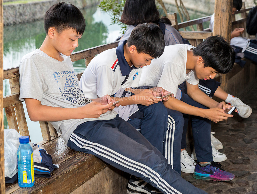 Yantou, Yongjia, Zhejiang, China.  Teenage Boys on Lishui Street Examining Their Cell Phones.