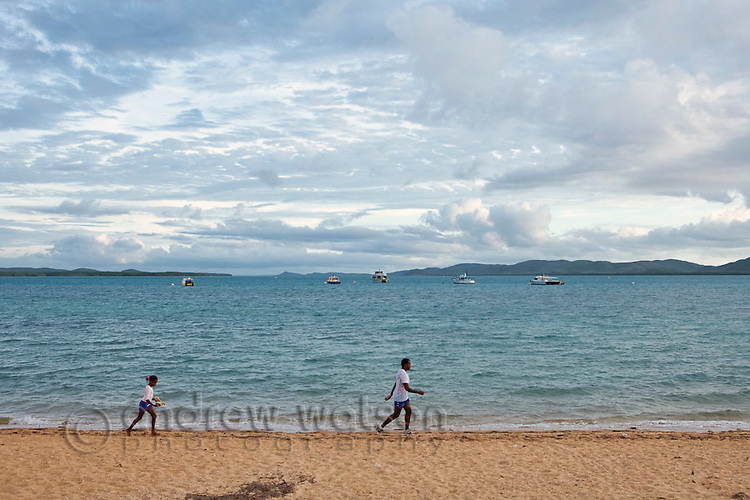 Locals walking along the beach on the Victoria Parade foreshore.  Thursday Island, Torres Strait Islands, Queensland, Australia