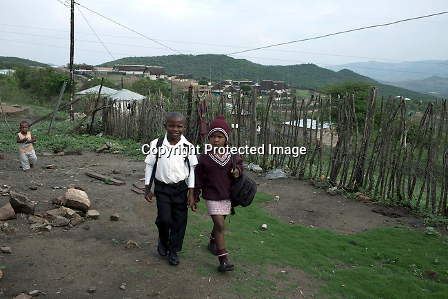 NKANDLA, SOUTH AFRICA - OCTOBER 10: Children walk to school close to South Africa president Jacob Zuma's new private residence in his birth village on October 10, 2012 in KwaNxamalala, Nkandla. South Africa.  The South African government is spending R240-million (about US$ 27 million) to construct the vast property for his large family. (Photo by Per-Anders Pettersson)