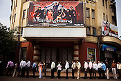 Passengers wait in queue for a bus outside a cinema in Mumbai, India.