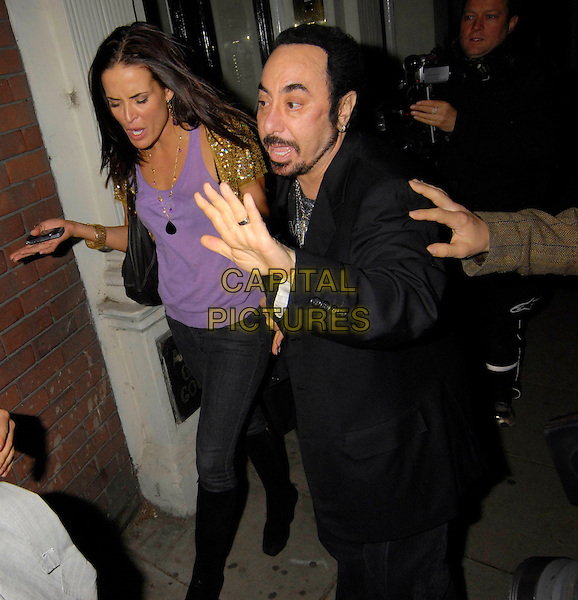 SOPHIE ANDERTON & DAVID GEST.Outside The Wellington Club, London, England,.November 5th 2007..full half 3/4 length purple top black jeans knee high boots gold sequined shrug funny hands .CAP/SW.©Capital Pictures.