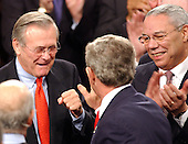 United States President George W. Bush gets some words of encouragement from United States Secretary of Defense Donald Rumsfeld, left, as United States Secretary of State Colin Powell, right, looks on as he arrives in the United States House of Representatives Chamber in Washington, D.C. on January 20, 2004.<br /> Credit: Ron Sachs / CNP
