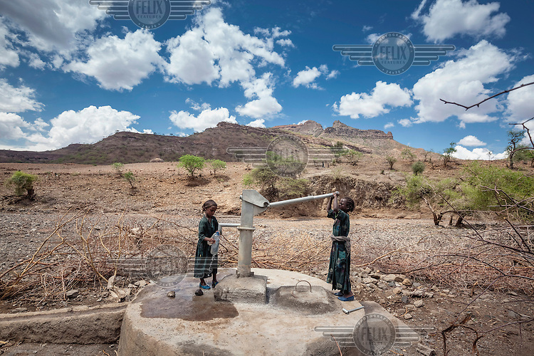 Two girls fill a bottle with water from the newly constructed village well. <br /> Ethiopia is experiencing its worst drought in over 50 years. The emergency started early in 2015 with the failure of the February-April 'Belg' rains and was further compounded by the main 'Kiremt' rain season (July-September) being erratic and poor, caused by an exceptional El Nino event.