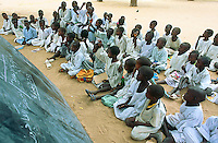 Sudan. West Darfur. Habilah. Public school. The children sit on the ground, listen to their teacher and the lesson. They also read the words written on the blackboard.  © 2004 Didier Ruef