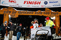 Pete Kaiser recieves his winning check, albeit blank, from GCI representive Bob James at the Nome finish line after winning the 2019 Iditarod Trail Sled Dog Race. Pete's winning time is 9 days 12 hours 39 minutes and 6 seconds<br /> <br /> Photo by Jeff Schultz/  (C) 2019  ALL RIGHTS RESERVED