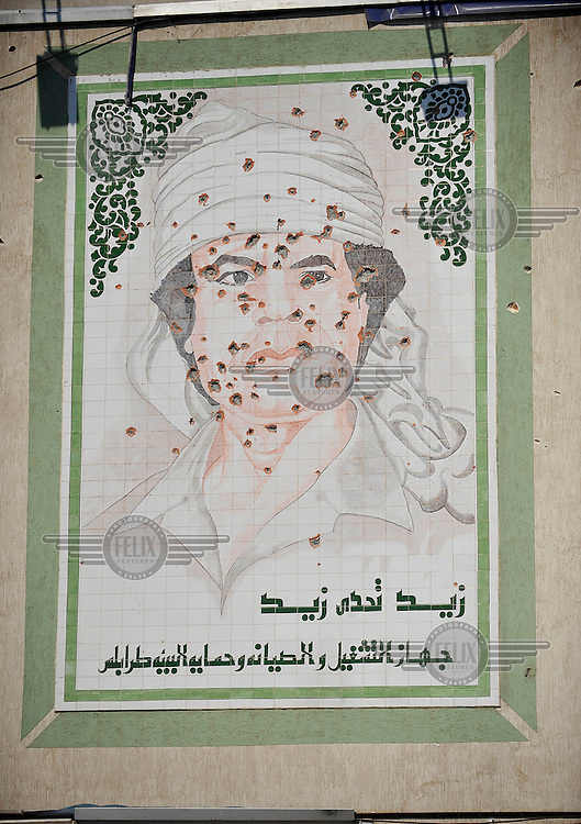 A shelled mural of Gaddafi on a wall off a street in Tripoli. After a six month revolution, rebel forces finally managed to break into Tripoli and have taken control of Bab al-Aziziyah, Col Gaddafi's compound and residence. Few remain that are loyal to Gaddafi in the city; it is seeming that the 42 year regime has come to an end. Gaddafi is currently on the run.