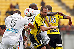 Phoenix's Andrew Durante, centre right, winces as he attempts to head the ball in the midst of Perth Glory players during the A-League football match at Westpac Stadium, Wellington, New Zealand, Sunday, March 09, 2014. Credit: Dean Pemberton